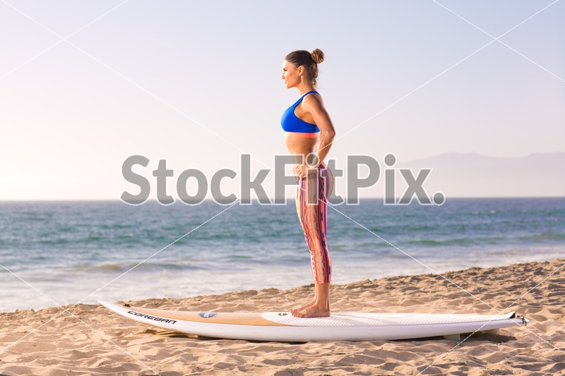 Lauren Abraham;Woman;Female;Brunette;Fitness;Model;Fit;Strong;Healthy;Lifestyle;Beautiful;Pretty;Hot;Sexy;Outdoors;Beach;Sand;Water;Daylight;Sunny;Leggings;Paddleboard;Surfboard;Training;Workout;Working out;Mountain pose;Standing;Hands on hips;Yoga