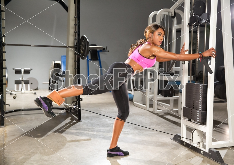 Mimi Macias;Woman;Female;Fit;Fitness;Strong;Healthy;Gym;Equipment;Weights;Leg training;Glute training;Working out;Workout;Pink top;Black leggings;One leg;Cable;Kickback